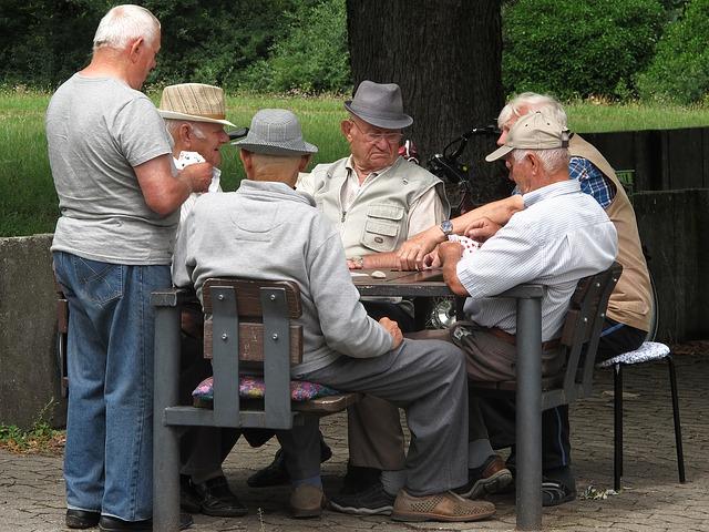 muži důchodci hrají karty